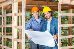 Confident Construction Workers With Blueprint At Royalty Free Stock Photos