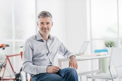 Confident contemporary businessman sitting in his office and smiling at camera royalty free stock photography