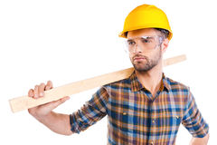 Confident contractor. Confident young male carpenter in hardhat and protective eyewear carrying wooden balk on shoulder while standing against white background Royalty Free Stock Image