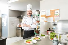 Confident Cook In Uniform At Kitchen. Mid adult chef smiling while crossing arms at kitchen counter stock images