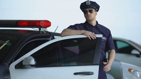 Confident cop getting out from car, wearing sunglasses and going to crime scene. Stock footage stock video