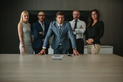Confident corporate professionals in meeting room. Portrait of confident multi ethnic group of businesspeople looking at camera while standing together at Stock Images