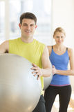 Confident Couple With Fitness Balls In Gym Stock Photography