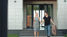 Confident couple going out modern building. Closeup rich couple going outside. Apartments with bag. Successful couple going down stairs with luggage stock video