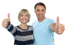 Confident couple showing thumbs up sign. To the camera, embracing each other Stock Images
