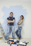 Confident Couple Standing Against Wall With Painting Tools In Fo Royalty Free Stock Images