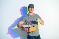 Confident courier gesticulating hand. Portrait of reliant man pointing finger in camera. He keeping package with documents. Painted reflection. Conveyance Stock Image