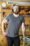 Confident craftsman with safety mask and earmuffs in workshop Royalty Free Stock Images