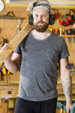 Confident craftsman with safety mask and earmuffs in workshop Stock Photography