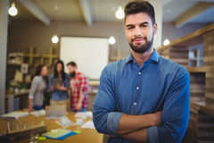 Confident creative businessman standing with arms crossed Stock Photos