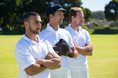 Confident cricket players standing at grassy field. On sunny day royalty free stock photo