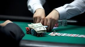 Confident croupier matching bet of casino client going all-in with money and key. Stock photo royalty free stock photos