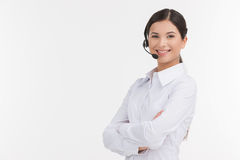 Confident customer service representative. Beautiful young female customer service representative in headset holding her arms crossed and looking at camera Stock Photography