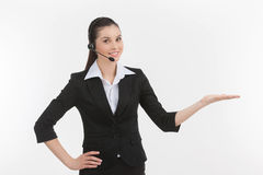 Confident customer service representative. Cheerful young female customer service representative in headset gesturing while isolated on white Stock Image