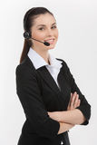 Confident customer service representative. Cheerful young female customer service representative in headset holding her arms crossed and looking at camera while Royalty Free Stock Images