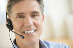 Confident Customer Service Representative Wearing Headset. Close-up portrait of confident male customer service representative wearing headset Stock Photos