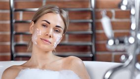Confident cute sexy young girl enjoying beauty moisturizing mask on face taking bath close-up stock video