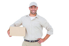 Confident delivery man with cardboard box on white background Royalty Free Stock Photos