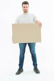Confident delivery man carrying cardboard box Royalty Free Stock Photo