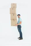 Confident delivery man carrying stack of boxes