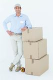 Confident delivery man leaning on stacked cardboard boxes Stock Photography