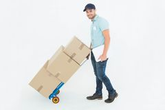 Confident delivery man pushing trolley of boxes