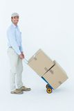 Confident delivery man pushing trolley of cardboard boxes Stock Photo