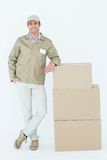 Confident delivery man standing by stack of boxes Royalty Free Stock Photo
