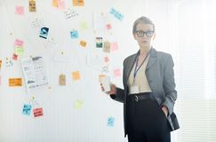 Confident detective. Mature female detective in formalwear standing by whiteboard in office royalty free stock image
