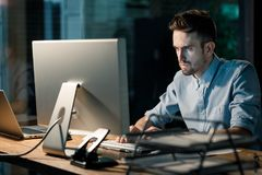 Focusing man working with computer in office stock image