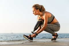 Confident disabled athlete woman with prosthetic leg. Tying shoelace outdoor royalty free stock photography