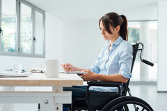 Confident disabled businesswoman at work. Confident disabled business woman in wheelchair working at office desk and checking paperwork Royalty Free Stock Images