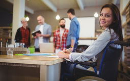 Confident disabled businesswoman writing at desk stock photo