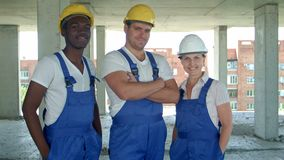 Confident diverse team of workmen and women standing grouped in their dungarees and hardhats smiling at the camera stock video