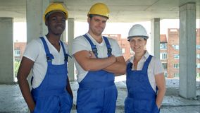 Confident diverse team of workmen and women standing grouped in their dungarees and hardhats smiling at the camera. Professional shot in 4K resolution. 104 Stock Photography