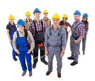 Confident diverse team of workmen and women. Standing grouped in their dungarees and hardhats smiling at the camera  high angle view isolated on white Royalty Free Stock Image