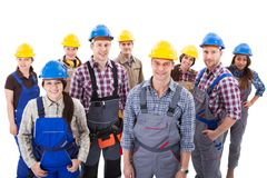 Confident diverse team of workmen and women. Standing grouped in their dungarees and hardhats smiling at the camera  high angle view isolated on white Royalty Free Stock Photos