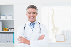 Confident doctor with arms crossed standing in clinic Royalty Free Stock Images