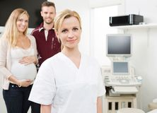 Confident Doctor With Expectant Couple In. Portrait of confident young doctor with expectant couple in background royalty free stock image