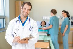 Confident Doctor Holding Clipboard While Nurses stock images