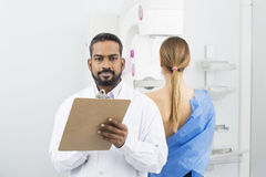 Confident Doctor Holding Clipboard While Patient Undergoing Mamm royalty free stock images
