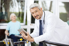 Confident Doctor Holding Digital Tablet While Leaning On Bar Stock Photography