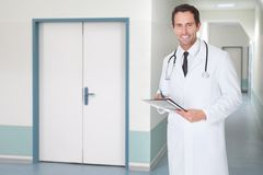 Confident doctor holding file in hospital corridor Royalty Free Stock Photo