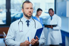 Confident doctor holding folder in clinic with colleagues behind Royalty Free Stock Photos