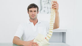 Confident doctor holding skeleton model in his office Royalty Free Stock Photography