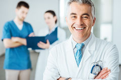 Confident doctor at hospital posing. Confident doctor posing and smiling at camera and medical staff checking medical records on background Royalty Free Stock Photos