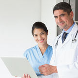 Confident doctor and nurse using laptop Stock Photo