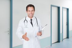 Confident doctor offering handshake while holding clipboard Royalty Free Stock Images