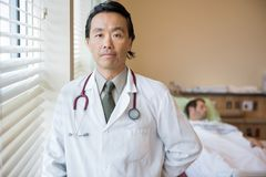 Confident Doctor With Patient In Background At. Portrait of confident male doctor with patient lying in background at hospital room stock photography