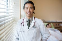 Confident Doctor With Patient At Hospital Room Stock Images